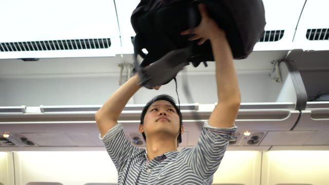 Man putting luggage on the top shelf on airplane, Travel video