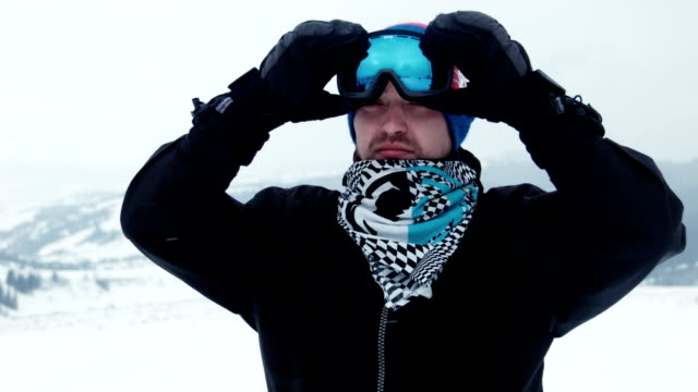 Man putting on his ski goggles, glasses in winter video