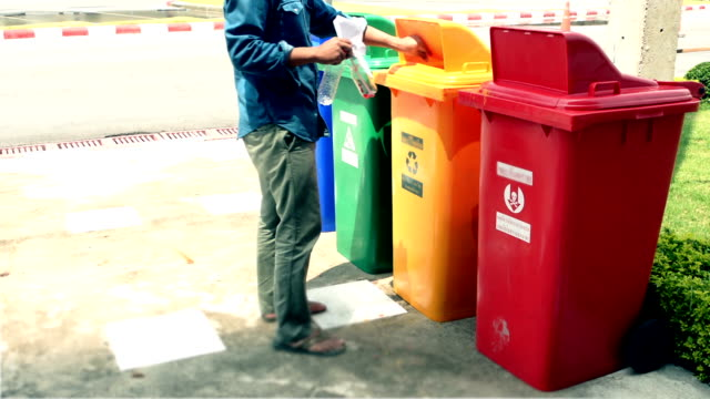 Man putting plastic bottles in recycle container. video