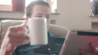 Man reading an article on his tablet and drinking tea video