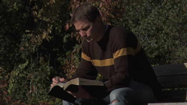 Man reading Bible on Bench 2 video