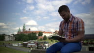 Man reading book on the wall by the river. video
