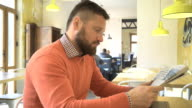 Man reading, browsing, daily newspaper, profile, in cafe, steadicam shot video