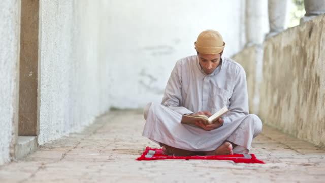 HD DOLLY: Man Reading Koran At Mosque Corridor video