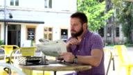 Man reading newspaper during breakfast and looks at camera video