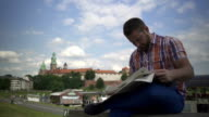 Man reading newspaper on the wall by the river. video