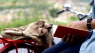 man reading old traveling book and plan the trip by vintage bicycle video