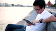 Man reading on his tablet at riverside video