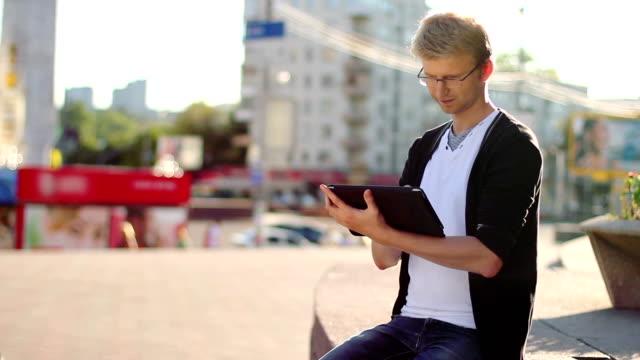 Man reading tablet pad writing browsing photos, looking camera video