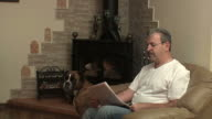 Man reads newspaper sitting in the armchair video