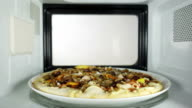 Man reheating baked seafood pizza in the microwave oven. video