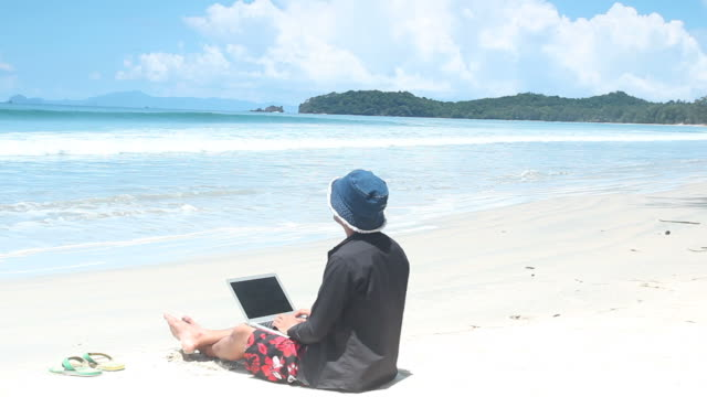 Man relax and playing laptop on the beach video