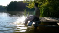 Man relaxes by the lake or pond sitting on the edge of a wooden jetty, swing one's feet in the water. Male legs splashing water in the pond. A person's feet relaxing and dangling in a river. Close-up video