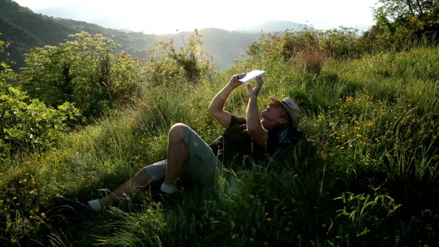 Man relaxes on grassy hillcrest at sunrise, uses digital tablet video