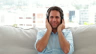 Man relaxing on the couch listening to music video