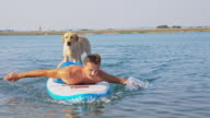 Man relaxing on the paddleboard with his dog video