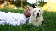 man relaxing with his senior dog in the meadow video