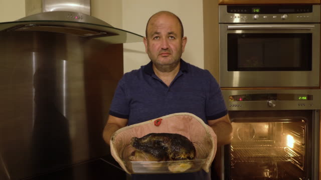 Man removing a burnt chicken from oven video
