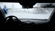 Man removing snow of Windshield During a Snowstorm video