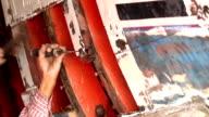 A man repairing wooden boat video