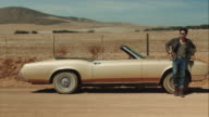 Man resting with retro car on dirt road video