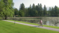AERIAL Man riding a bicycle along the lake in a beautiful park video