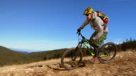 SLO MO Man riding his bike down mountain trail video