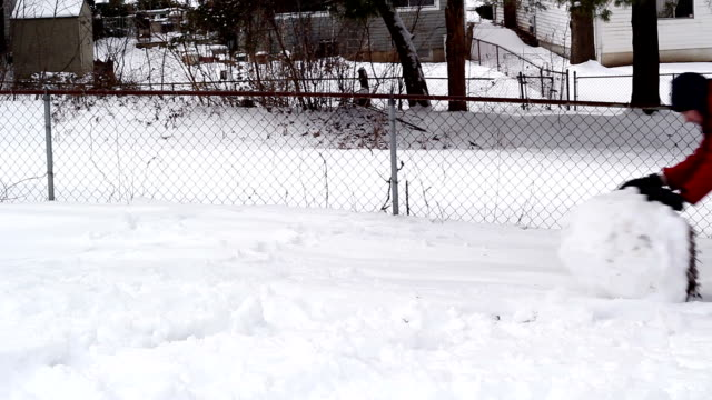 Man Rolling a Large Snow Ball video