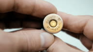 Man rotates in hand and carefully examines the new hunting cartridge. Macro video