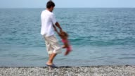 Man rotating little girl on pebble beach video