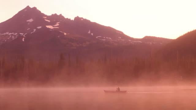 Man rowing canoe on misty lake at sunrise video