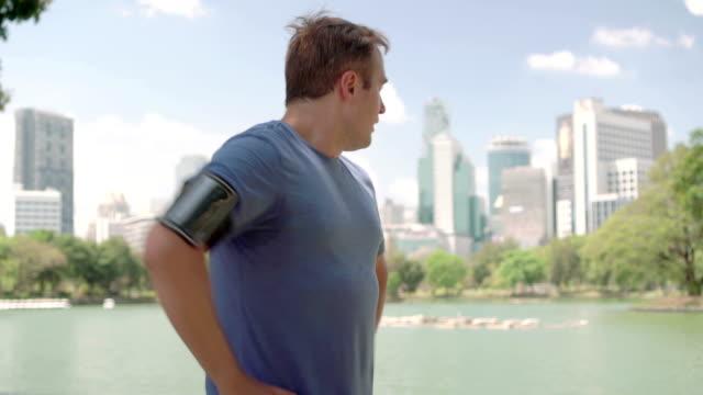 Man runner jogging in park. Fit male sport fitness running training. Having a rest video