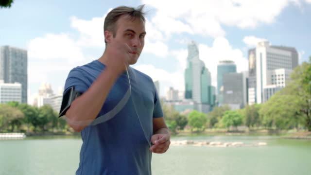 Man runner jogging in park. Fit male sport fitness running training. Listen music on smartwatch video
