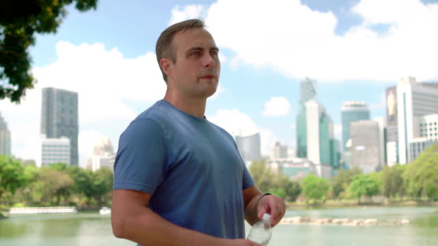 Man runner jogging in park. Fit male sport fitness running training. Drinking water from bottle video