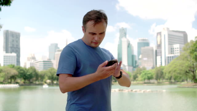 Man runner jogging in park. Fit male sport fitness running training. Talking on his smartphone video