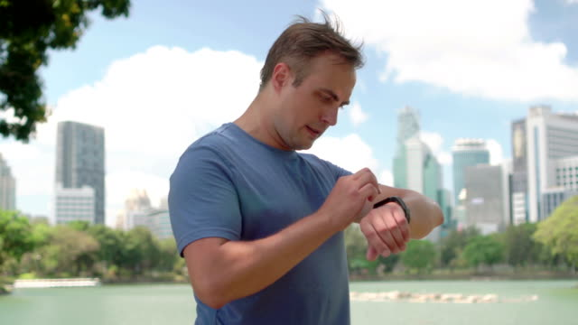 Man runner jogging in park. Fit male sport fitness running training. Using smartwatch checking cellphone video
