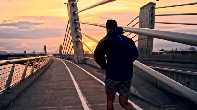 TS Man Running Across The Bridge At Sunrise video