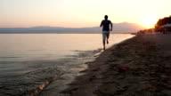Man running along a beach at sunset video