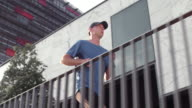SLO MO TS Man running along a business building video