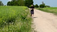 Man running along the edge of the rural road in summer video