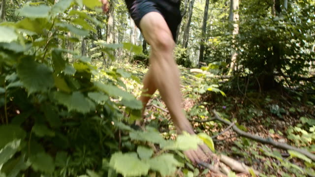 Man running barefoot across forest undergrowth video