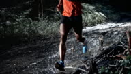 SLO MO DS Man running on a muddy forest trail at night video