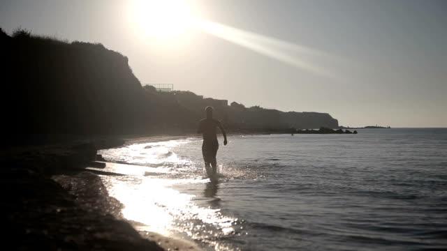 Man running on beach at sunrise video