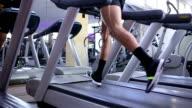 Man running on treadmill closeup on his legs in slow motion video