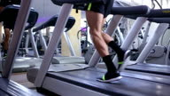 Man running on treadmill closeup on his legs video