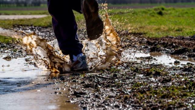 SLOW MOTION : Man running through muddy puddle video