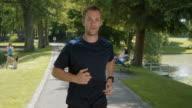 SLO MO TS TU Man running through park in sunshine video