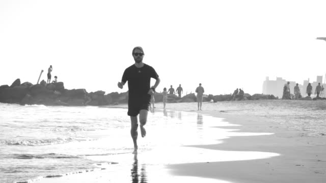 A man runs on the beach at sunset - 240 fps slow motion video