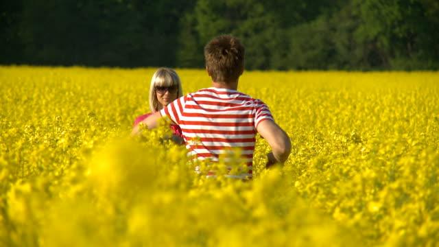 HD: Man runs towards woman in the oilseed rape field. video