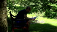man sad reaction after reading letter sitting on bench in park. FullHD video